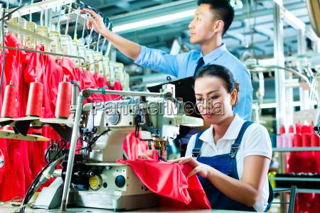 naeherin und schichtleiter in einer textilfabrik