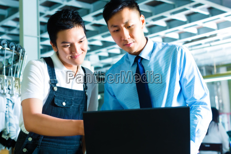 worker and supervisor with laptop in
