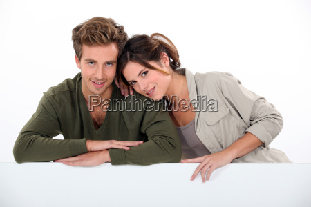 couple leaning on blank poster