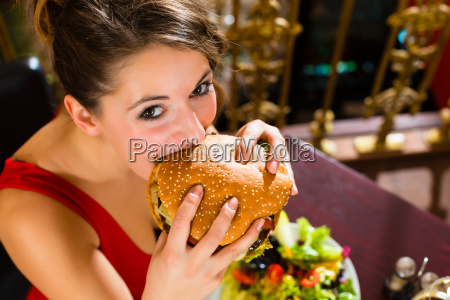 young woman in fine restaurant eating