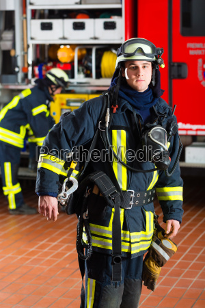 firefighter standing in uniform in front
