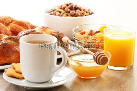 fruehstueck mit kaffeebrothonigorangensaftmuesli ein