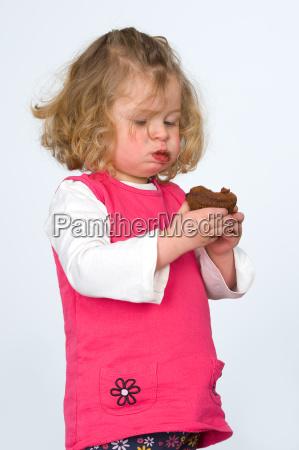 little girl is eating chocolate cake