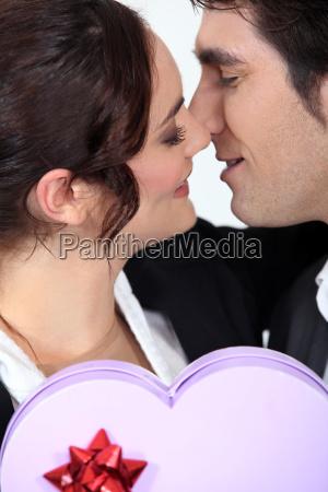 man offering girlfriend heart shaped box