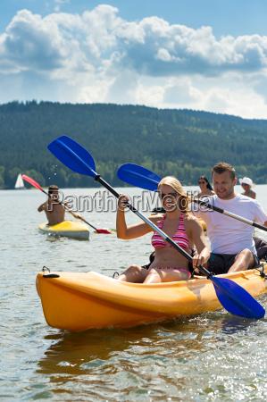 smiling couple rowing kayak sunshine