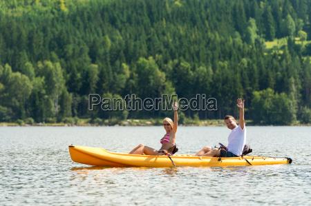 man and woman kayaking on pond