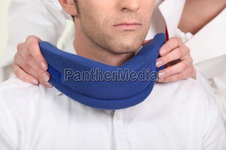 nurse attaching a neck brace for
