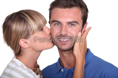 young woman kissing a mans cheek