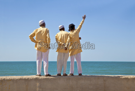 men standing on a wall waving