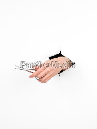 female hand holding pair of scissors