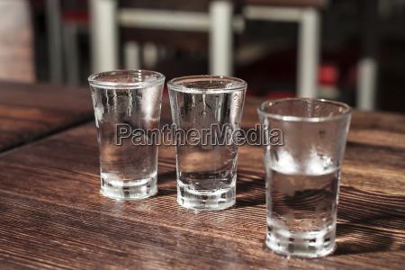 schuss glaeser wodka auf einem holztisch