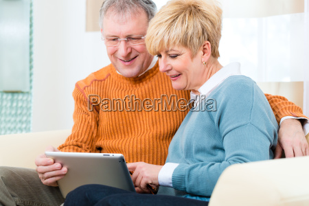pensioners at home with tablet computer