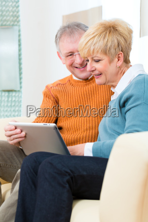retiree at home with tablet computer