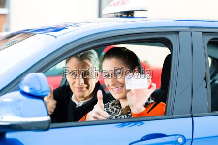junge frau in einem fahrschulauto