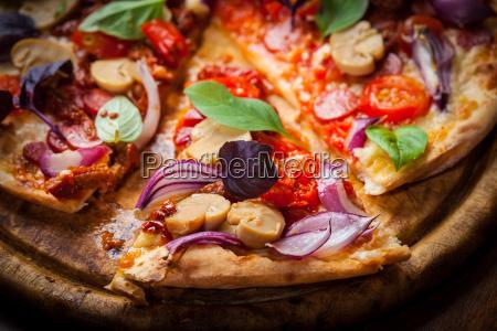 hausgemachte pizza mit getrockneten tomaten und