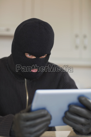 burglar looking at tablet pc