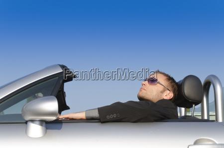erfolgreicher geschaeftsmann in einem cabrio relaxet