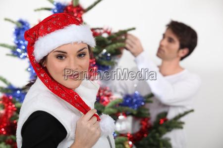 frau mit weihnachtsmuetze und mann dekoration