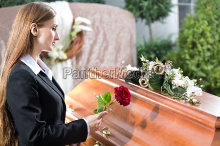 frau auf beerdigung mit sarg