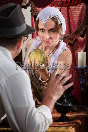 pretty fortune teller holding crystal ball