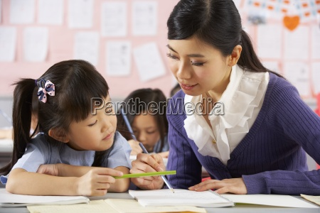 teacher helping student working at desk