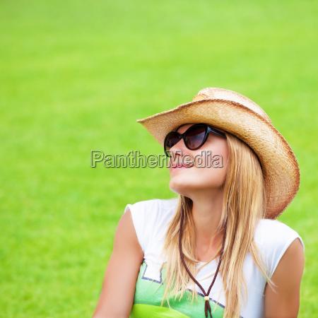 glueckliche frau auf gruenem gras