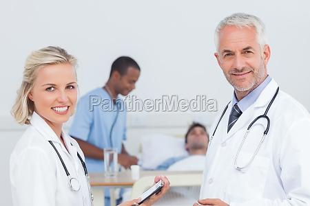 laechelnd aerzte stehen vor der patienten