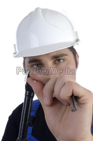 junger bauarbeiter mit hammer und naegeln