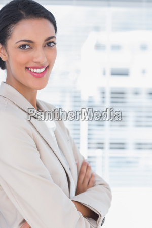 cheerful businesswoman with arms crossed standing