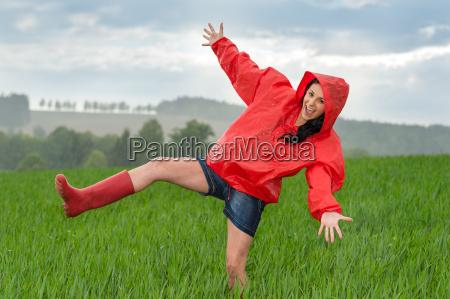 spielerisch teenager maedchen tanzt im regen