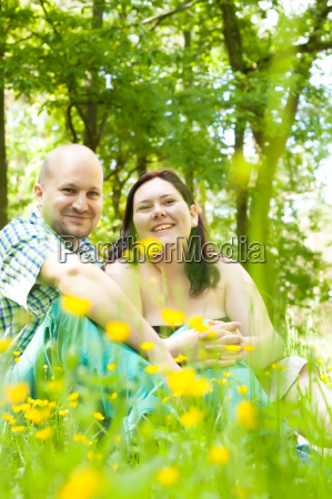 happy young married couple between flowers