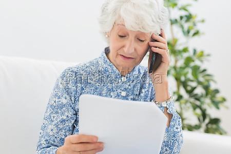 aeltere frau liest papiere am telefon