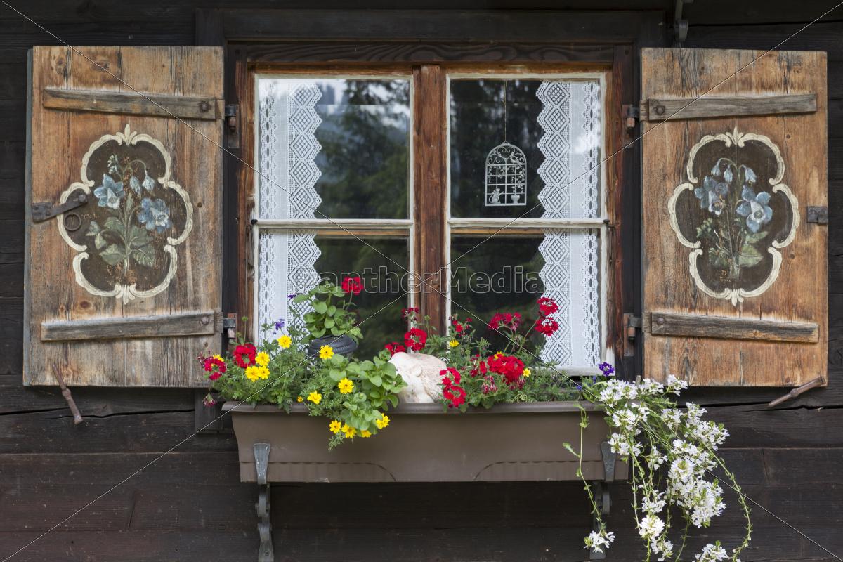 Stock Bild 9588386 - Fenster einer Almhütte mit Blumenkasten