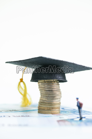 miniature student looking at the mortarboard