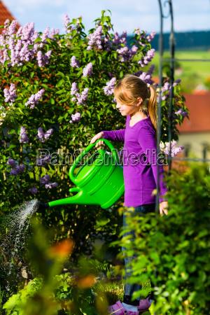 glueckliches kind giesst blumen im garten