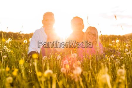 glueckliche familie auf wiese bei sonnenuntergang