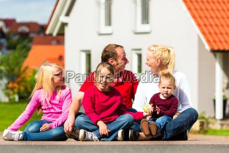 glueckliche familie sitzt vor ihrem haus