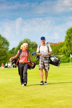 junges sportliches paar beim golfen am