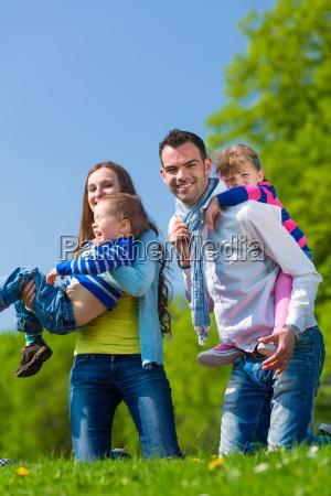 glueckliche familie spaziert auf sommer wiese