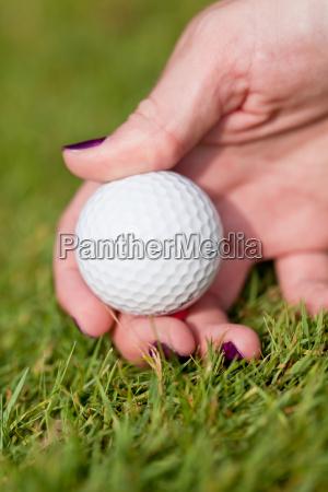 golfball und golfschlaeger tee auf gruenem