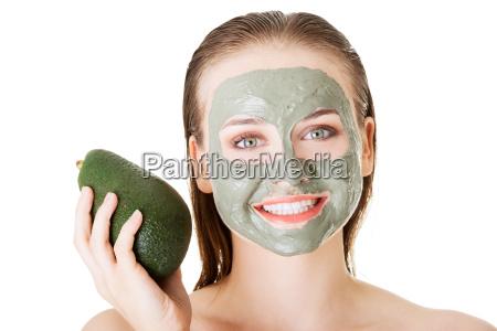 schoene frau mit gruenem avocado lehmgesichtsbehandlungschablone