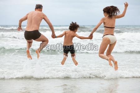 glueckliche familie spass am strand im