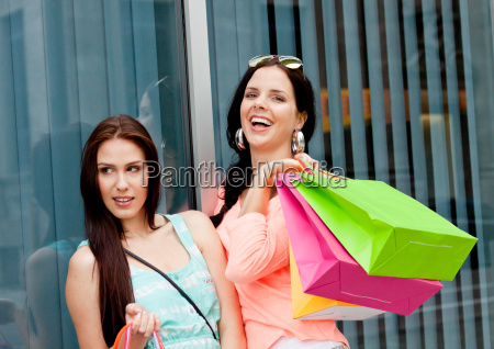 two young women laughing while shopping