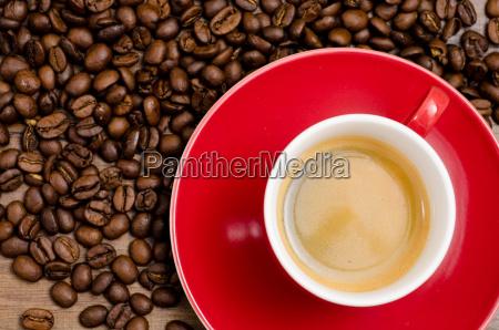 rote tasse espresso und braune kaffeebohnen