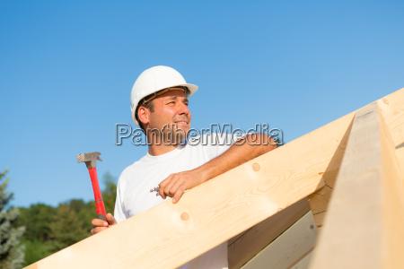 junger bauarbeiter am dachstuhl eines neuen