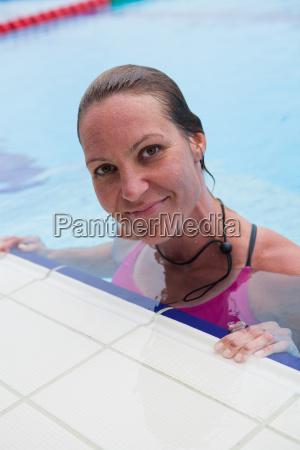 weiblicher schwimmer am poolrand