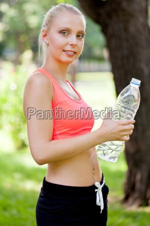 junge attraktive sportliche frau trinkt wasser