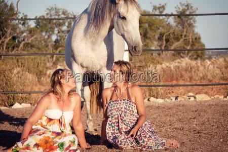 zwei erwachsene frauen mit pferd und