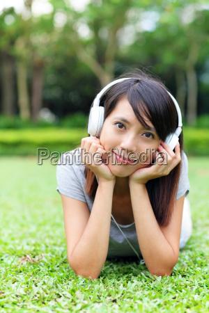 asiatische frau hoert lied auf gras