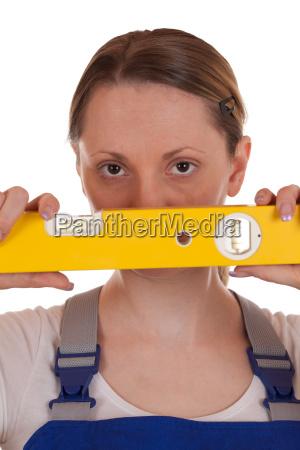 junge handwerkerin mit wasserwaage in der